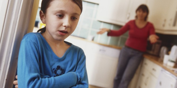 Girl standing in doorway of kitchen, arms folded, woman standing behind, arms extended.